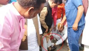 Staff cleans Ministers sandals in a official event - Sakshi