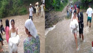 couple braves storm wades through floodwater to get married  - Sakshi