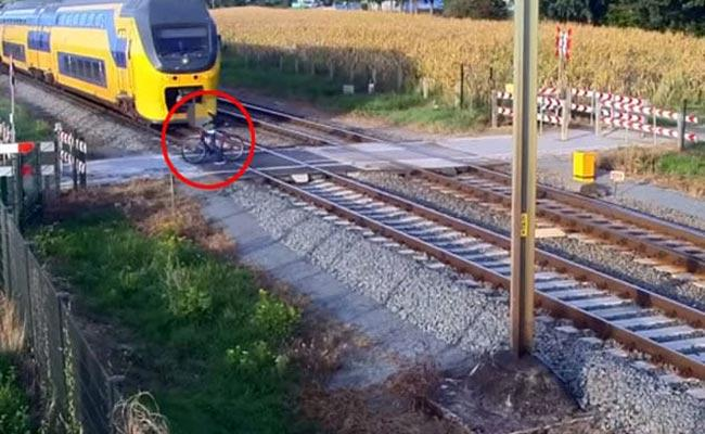 Netherland Cyclist Narrowly Escape Oncoming Train By A Split Second - Sakshi