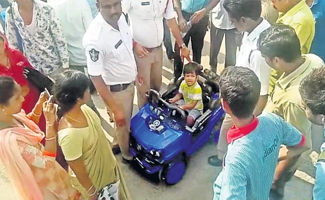 Boy Drives Toy Battery Car Into Busy Road In Vijayawada - Sakshi