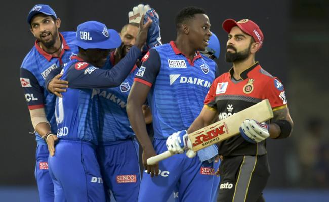 DC down RCB to reach playoffs - Sakshi