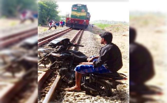 Young Man Arrest in Bike Stands on Train Track in Tamil Nadu - Sakshi