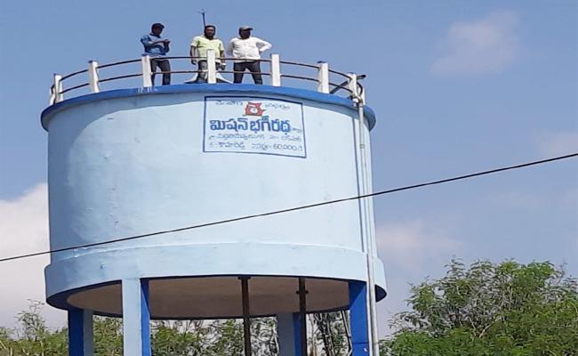 Man Climbing Water Tank For Protest Temple - Sakshi