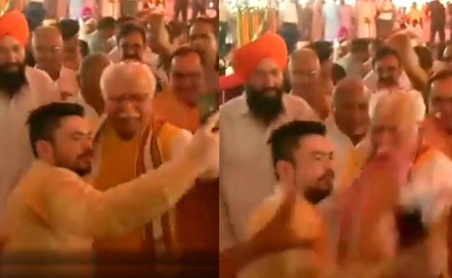 CM Manohar Lal Khattar pushes aside a man who tries to take a selfie with him - Sakshi