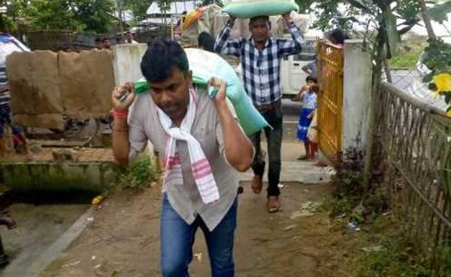 Assam MLA picks up rice bags flood affected people - Sakshi