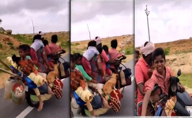 Viral Video Man Rides Bike With 7 People And 2 Dogs - Sakshi