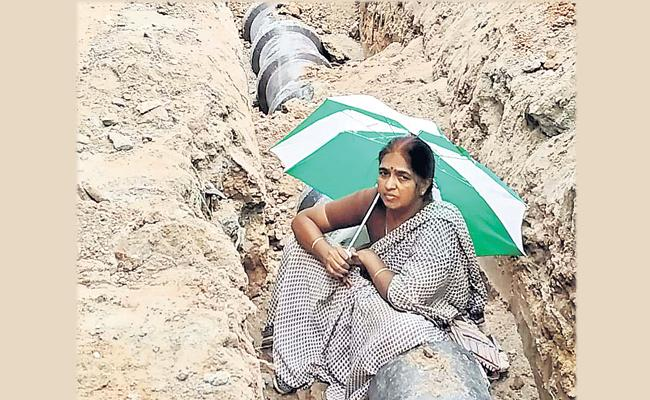 Woman Protest Sitting In Drainage At Madhapur In Hyderabad - Sakshi