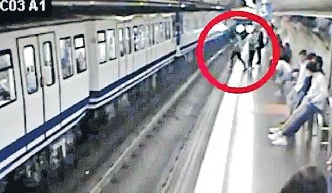 Woman on phone slips and falls in front of train - Sakshi