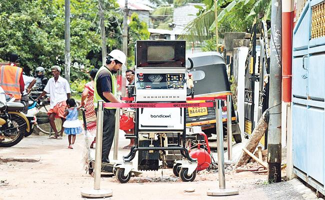 TS Government Use Bandicoot Robot For Cleaning Manholes - Sakshi
