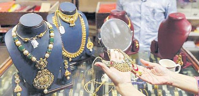 Gold prices hold above 1,300 dollors on US rate pause hopes - Sakshi