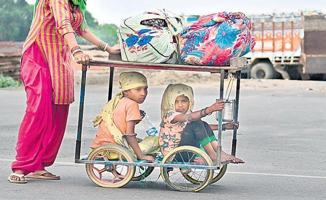 Women Migrants Carrying Children On Roads Due To Lockdown - Sakshi