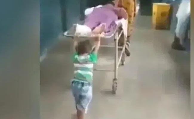 UP hospital ward boy removed after 6yrold pushes grandpa stretcher - Sakshi