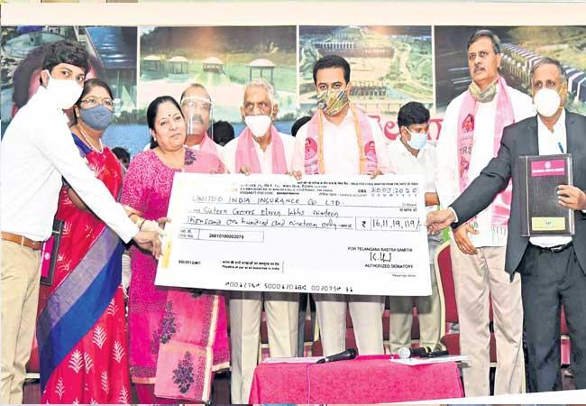 KTR Giving Insurance Checks In Telangana Bhavan - Sakshi
