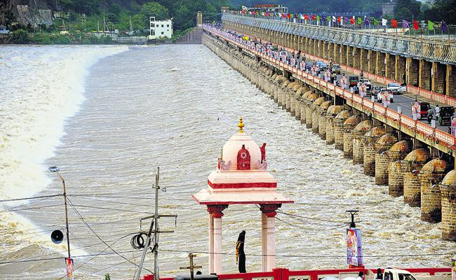 Above Six lakh cusecs flood flow into Prakasam Barrage - Sakshi
