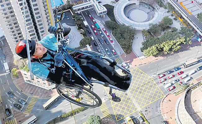 Hong Kong: On Wheelchair Paraplegic Lai Chi wai Climbs Up Skyscraper - Sakshi