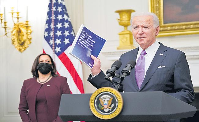 US President Joe Biden signs burst of virus orders - Sakshi