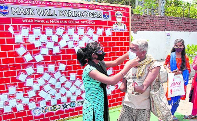 Women Help Handicapped Person For Wearing Mask - Sakshi