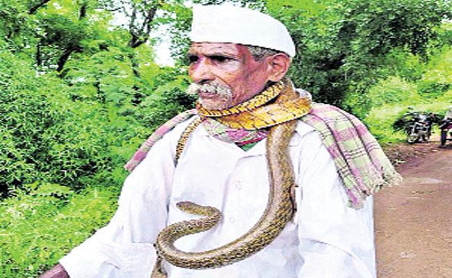 Karnataka Man With Snake Around His Neck On Cycle Goes Viral - Sakshi